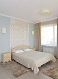 Interior of a double hotel room in light tones with a double bed Stock Images