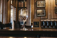 Interior of The Eagle Cambridge pub, empty wine glass on the table. royalty free stock image
