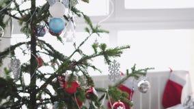 Interior elegante de la Navidad blanca con el árbol de abeto adornado por la ventana y foco de los cambios de empañado a enfocado metrajes