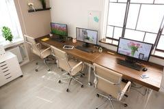 Interior elegante del lugar de trabajo con los ordenadores imagen de archivo