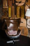 Interior elegante en estilo del desván yeso texturizado gris en las letras de madera de la pared butaca cómoda hecha del cuero ma imagen de archivo