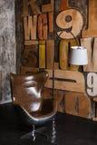 Interior elegante en estilo del desván yeso texturizado gris en las letras de madera de la pared butaca cómoda hecha del cuero ma foto de archivo libre de regalías