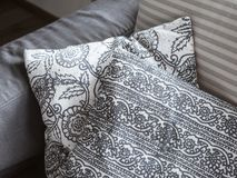 Interior element. Decorative pillows with floral pattern lie on a soft sofa. Closeup.  stock photo