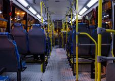 Interior of an empty collective bus at night seen from the bottom chairs. Pattern in lamps and pipes Stock Photo