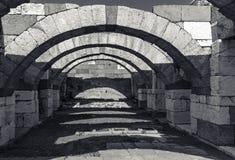 Interior of empty corridor with arcs. Ancient Smyrna. Izmir. Interior of empty corridor with arcs. Ruins of Ancient city Smyrna. Izmir, Turkey. Black and white Stock Image