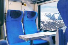 Interior of an empty passenger train with blue chairs and mountain views outside the window while driving Royalty Free Stock Photos
