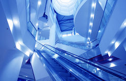 Interior of empty shopping mall toned in blue. Bright interior of empty shopping mall with multi-level escalators toned in blue Stock Photo