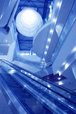 Interior of empty shopping mall toned in blue. Bright interior of empty shopping mall with multi-level escalators toned in blue stock photography