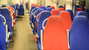 Interior of an empty train with red and blue seats. The interior of an empty train with red and blue seats stock video