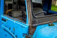 Interior enorme azul abandonado del coche de la dirección de la hierba verde del coche del vintage Foto de archivo libre de regalías