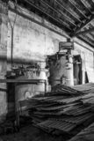 Interior Equipment and Pile of Tin in Black and White Interior of Old Building royalty free stock photography