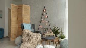 Interior escandinavo do Natal à moda com uma poltrona elegante e uma manta morna dos merinos Casa do conforto com novo nórdico filme