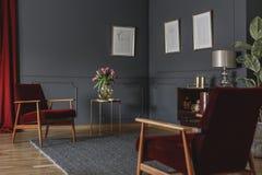 Interior espacioso de la sala de estar con las butacas rojas, tulipanes rosados, g Fotografía de archivo libre de regalías