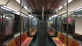 Interior of Empty New York City Subway Car. An interior establishing shot of an empty New York City subway car as it travels along the tracks. Loopable, with stock footage