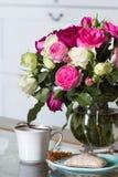 Interior fêmea - ramalhete de rosas inglesas perfumadas do rosa e as brancas, escudos e vela cor-de-rosa na tabela de vidro foto de stock