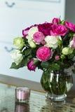 Interior fêmea - ramalhete de rosas inglesas perfumadas do rosa e as brancas, escudos e vela cor-de-rosa na tabela de vidro imagens de stock royalty free