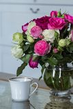 Interior fêmea - ramalhete de rosas inglesas perfumadas do rosa e as brancas, escudos e vela cor-de-rosa na tabela de vidro fotos de stock
