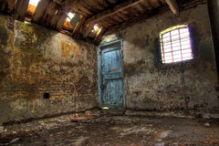Interior of farm building. Interior of old farm building with holes in the wooden roof, barred window, cracked walls and green door with peeling paint Royalty Free Stock Image