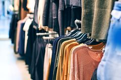 Interior of fashion clothes store with different women clothes on hangers in various colors. royalty free stock images