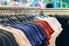 Interior of fashion clothes store with t-shirts on hangers in red, blue and other colors. stock photo