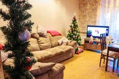 Interior festivo del día de fiesta, árbol de navidad, TV, sofá Foto de archivo