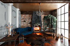 Interior with fireplace, candles, skin of cows, brick wall, large window and a metal cell of a loft, living room, coffee Stock Images