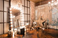 Loft interior with mirror, candles, brick wall, large window, living room, coffee table in modern design. Interior with fireplace, candles, skin of cows, brick Royalty Free Stock Photo