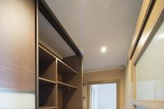 Interior of the flat. Warm tones, wooden floor. Built-in wardrobe. Modern flat interior with laminate and warm tones. Built-in wardrobe Stock Photo