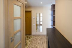 Interior of the flat. Warm tones, wooden floor. Modern flat interior with laminate  and warm tones. Furniture. Hall and doors Royalty Free Stock Photo
