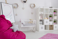 Interior full of pastel colors. Baby girl room in pastel colors with a book case, baby cradle, easel, and bean bag pink chair with star cushion stock photo