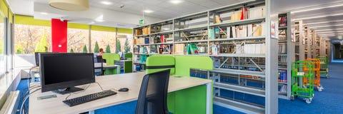 Interior funcional de la biblioteca con el escritorio foto de archivo