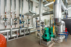 Interior gas boiler room with multiple pumps and piping Stock Photos