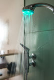 Interior of a glass shower cabin. With running water and moisture on glass. shower head has colored light Stock Images