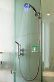 Interior of a glass shower cabin. With running water and moisture on glass. shower head has colored light Stock Photos
