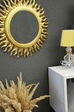 Elegant room interior with mirror on nightstand. Interior. gray wall. Mirror in the shape of the sun. Yellow night light, bedside table. Modern design, repair royalty free stock photos