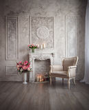Interior with grey fretwork background, fireplace and flowers.  Stock Photography