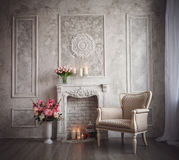 Interior with grey fretwork background, fireplace and flowers Stock Photos