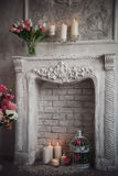 Interior with grey fretwork background, fireplace and flowers Stock Image