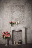 Interior with grey fretwork background, fireplace and flowers Royalty Free Stock Photography
