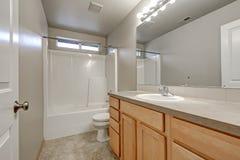 Interior gris del cuarto de baño con el gabinete de madera de la vanidad fotografía de archivo libre de regalías