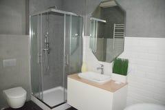 Interior gris del cuarto de baño con la parada de ducha con las paredes de cristal, fregadero del baño del espejo, fauset, wc Int fotografía de archivo