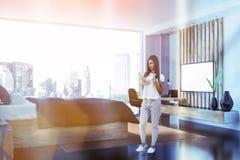 Interior gris del dormitorio con TV, mujer fotos de archivo libres de regalías