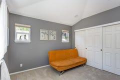 Interior gris del sitio con el sofá anaranjado brillante imagen de archivo