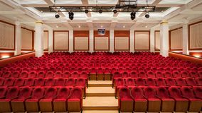 The interior of the hall in the theater. Concert hall of the theater with red new chairs. The interior of the hall in the theater or cinema view from the stage Royalty Free Stock Photo