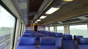 Empty interior of a passenger train car in motion. Interior of a high-speed train moving at high speed during the day in cloudy weather. Window view from fast stock footage