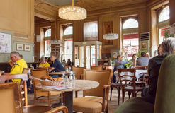Interior of historical cafe with pelaxing people, big windows and retro furniture. Vienna Stock Photography