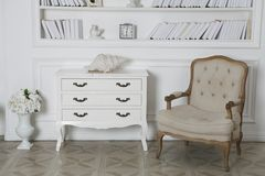 Interior of hite roomwith bookshelves, an armchair and a chest of drawers stock photo