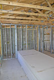 Interior Home Construction. Trusses and wood framing construction in a new house with stack of drywall wall boards Royalty Free Stock Image