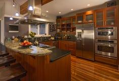 Interior home de gama alta contemporâneo da cozinha com armários e assoalhos de madeira, bancada do granito e dispositivos de aço