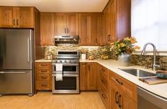 Interior home de gama alta contemporâneo da cozinha com os armários de madeira da cereja, as bancadas de quartzo, os assoalhos re foto de stock